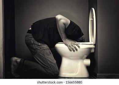 Man vomiting in toilet bowl