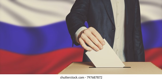 Man Voter Putting Ballot Into Voting box. Democracy Freedom Concept On Flag Background Toned Image