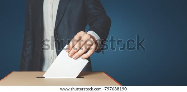 Mann Wähler, der die Wahl in die Abstimmungsbox bringt. Demokratisches Freiheitskonzept in der Nähe des Kopienraums