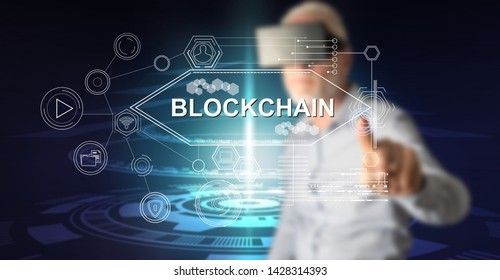 Man with vr headset touching a blockchain concept on a touch screen with his finger