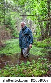 A man wades through a dangerous wetland in the Swedish wilderness.