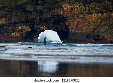Man wading through water at Hole in the Wall