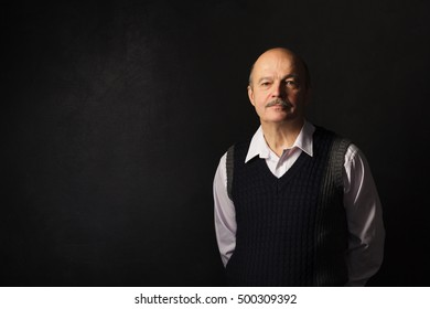 man in a waistcoat looking confidently forward. Lecturer stands in black chalk wall