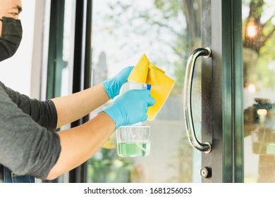 Man waiter hands with alcohol sanitizer door knob prevent the virus.