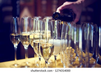 MAN WAITER PORTS CHAMPAGNE IN GLASS SHOPS ON CELEBRATIONS