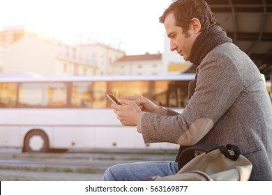 Man waiting at the bus station and looking at his smart-phone