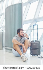 man waiting for his flight in the international airport and calling on phone