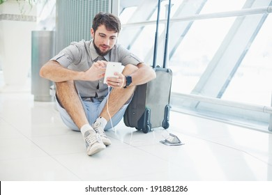 man waiting for his flight in the international airport and typing message on phone