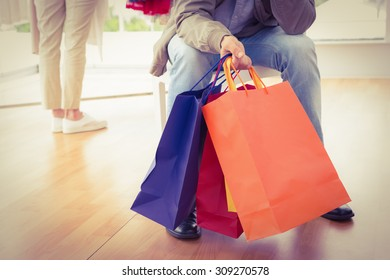Man waiting for his shopping woman in clothing store