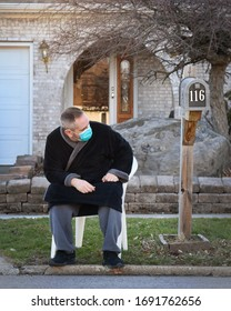 A man is waiting outside next to a mailbox for a concept regarding the coronavirus stimulus relief bill passed to help families during pandemic.