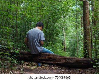 Man is waiting someone in the forest.