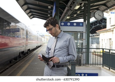 Man waiting for train while looking at his wallet.