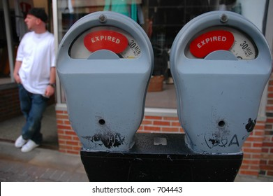 Man waiting while parking meters expire
