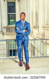 Man Waiting for You. Dressing formally in blue suit, patterned undershirt, tie, leather shoes, haircut, crossing arms, a young black businessman is sitting on railing in office building, relaxing,