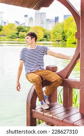 Man Waiting for You. Wearing a striped T shirt, brown corduroy pants, a young handsome guy is sitting by a lake, inclining half body, looking faraway, relaxing, fun.