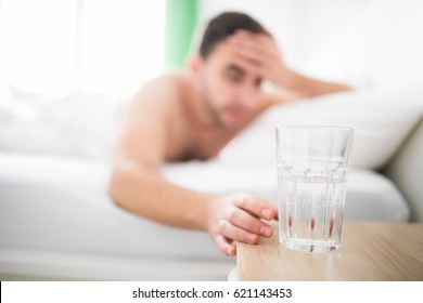Man wake up with head pain suffers from headache and extend to get a glass of water in his bed