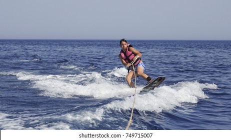 A man wakeboarder clings to a cable and moves behind a boat on the sea