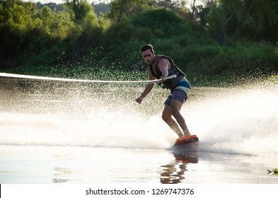 Man wakeboarding on lake behind boat. Water skiing on lake at sunset