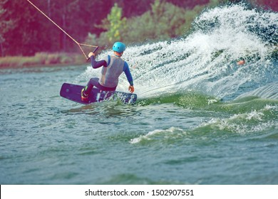 Man wakeboarding on lake behind boat. Water skiing on lake