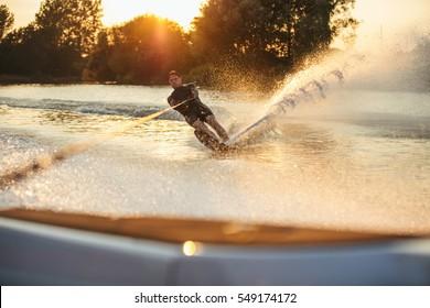 Man wakeboarding on lake behind boat. Water skiing on lake at sunset.