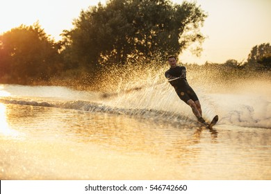 Man wakeboarding on a lake with splashes of water. Wakeboarder surfing across the lake.