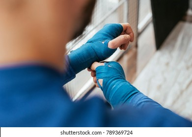 A man wakes a boxing bandage of blue in his arms. preparation for competitions, before the fight.