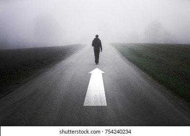 Man walk alone on foggy road with straight up arrow sign painted on the road.