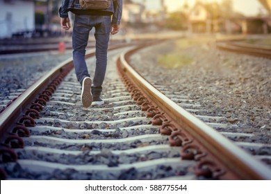 Man walk away on railroad with warm light.Selective focus.Traveler man on railroad.