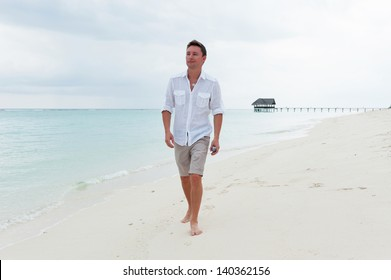 Man walk on the background of beautiful beach with white sand and cloudy sky