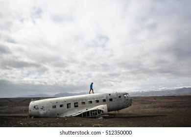 Man walk on epic plane wreck on the black beach in south Iceland