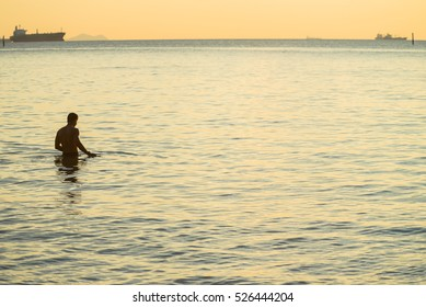 The man walk in the sea in sunset time