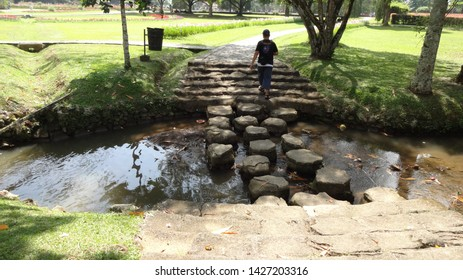 a man walk trought rocks bridge in the small river at nusantara flower garden, cisarua, indonesia. photo taken in june 2019