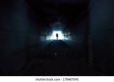 A man walking alone in the dark tunnel