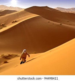 Man walking alone in the desert under the sun. Moroccan background.