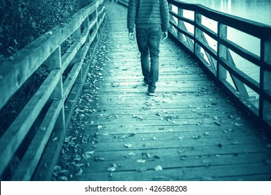 A man walking alone on aged wooden bridge floor with leaves on the ground. Cyan blue color effect and selective focus used.