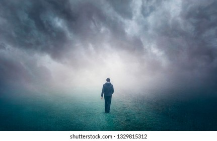 Man walking alone on misty foggy countryside field.