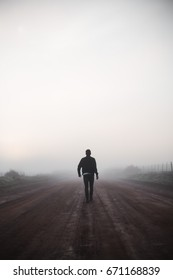 Man walking alone on misty road