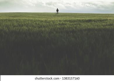 man walking alone on a wide grass field outdoor