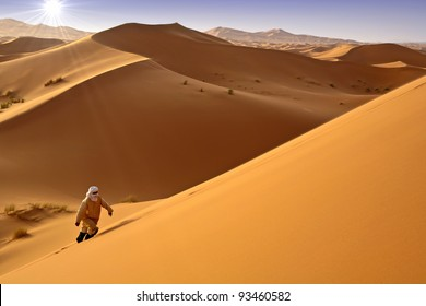 Man walking alone in the sunny desert. Moroccan dunes background.