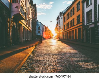 Man walking alone at sunset street Travel Lifestyle concept vacations cobblestone road city in Norway