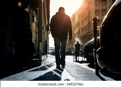 Man walking alone through the city road against sun