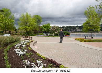 A man walking along the boardwalk at the Chicoutimi port on the Saguenay River in Quebec.