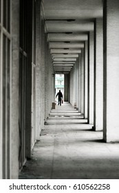 Man walking along a long corridor with columns
