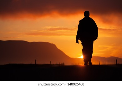 a man walking along the road, backlit at sunset, among the mountains, the clouds