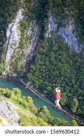 A man is walking along a stretched sling. Highline in the mountains. Man catches balance. Performance of a tightrope walker in nature. Highliner on the background of the mountains and river.