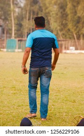 Man walking around a sports ground wearing jeans unique photo