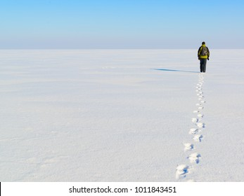 Man walking away and leaving his footprints on the endless empty snow field in a cold winter day