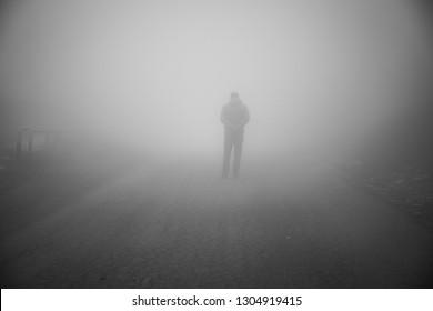 Man walking away on misty road. Man standing alone on rural foggy and misty asphalt road. Selective focus