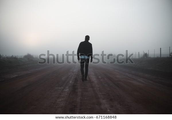 Man walking away on misty road