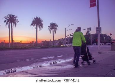 Man walking baby during sunset on San Pablo ave, Berkeley Ca. Circa 2017
